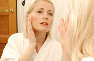 Woman applying lotion to her face